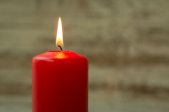Red Christmas candle. On a white wooden background Royalty Free Stock Images
