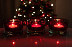 Red christmas candles. Three red glass candles burning and christmas tree in the background Royalty Free Stock Photo