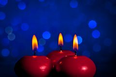 Red christmas candles on blue bokeh background Royalty Free Stock Image
