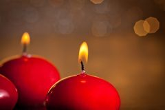 Red christmas candles on golden bokeh background Stock Photos