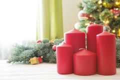 Red christmas candles on white wooden plank against christmas tree in living room.  Royalty Free Stock Image