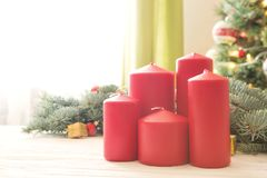 Red christmas candles on white wooden plank against christmas tree in living room.  Royalty Free Stock Photo
