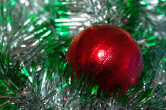 Red christmas decoration ball with green garland Royalty Free Stock Photo