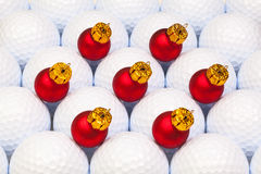 Red Christmas decoration between the golf balls Royalty Free Stock Photos