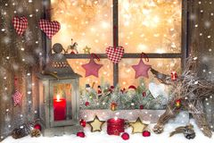 Red Christmas decoration with lantern on window sill with wood Royalty Free Stock Photography