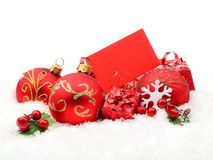 Red christmas decoration on snow with wishes card Royalty Free Stock Image