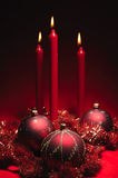 Red christmas decoration theme. Three red baubles and three red candles Royalty Free Stock Image
