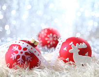 Red Christmas Decorations. On white material with a sparkling bokeh of silvery festive lights Royalty Free Stock Images