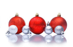 Red Christmas decorations. Red and silver Christmas decorations in a row with reflections and copyspace for your Christmas greetings or wishes royalty free stock images