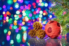 Red Christmas decorations ball with spruce. And cones on bokeh background Stock Image