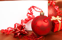 Red Christmas decorations and card. Red Christmas decorations and white card with copy space Royalty Free Stock Images