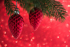 Red christmas decorations cones on the xmas tree on red glitter bokeh background. Stock Photo