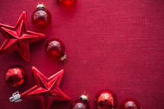 Red christmas decorations (stars and balls) on red canvas background. Merry christmas card. Stock Photo