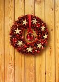 Red Christmas garland in old wooden door Stock Photography