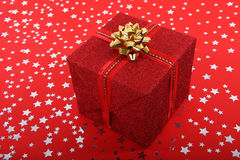 Red Christmas gift. Christmas gift on red background full of stars Royalty Free Stock Photos