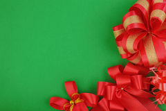 Red christmas gift bow and ribbon on green paper for background Royalty Free Stock Photo