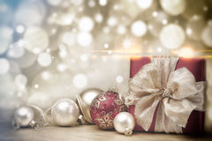 Red Christmas gift box and baubles on background of defocused golden lights. Red Christmas ball on golden blurred background stock images