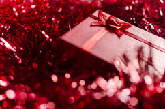 Red Christmas gift box on glossy red decoration Royalty Free Stock Photo