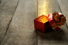Red Christmas gift box with gold magic lights on wooden desk Royalty Free Stock Photos