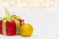 Red Christmas gift box. With shiny golden ball. Bokeh with glow effect on white background. Copyspace for your greeting or wishes royalty free stock photography