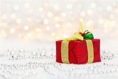 Red Christmas gift box. With shiny golden ribbon and metalic beads. Bokeh with glow effect on white background. Copyspace for your greeting or wishes royalty free stock photography