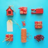 Red Christmas gift boxes and decorations on blue background. Flat lay. Top view. Toned stock photo