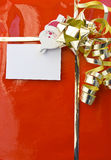 Red christmas gift with empty card. Detail of a decorated christmas gift and santa holding an empty card Royalty Free Stock Photos