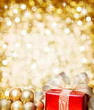 Red Christmas gift with gold baubles and golden background. Red Christmas gift with a golden ribbon and gold baubles with blurred bokeh copy space and sparkles Stock Image