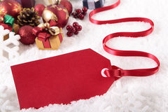 Red Christmas gift tag laying on snow background with various gifts and decorations Stock Photography