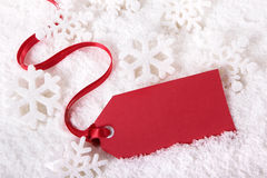 Red Christmas gift tag in snow background with snowflakes, copy space Royalty Free Stock Photo