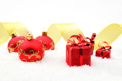 Red christmas gifts,baubles golden ribbon on snow Royalty Free Stock Photography