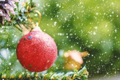 Red Christmas glitter ball decoration hanging on tree with snow effect Royalty Free Stock Photos