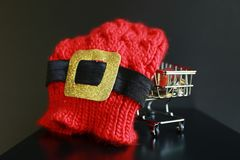 Red christmas hat, coins in mini trolley isolated in dark black background. Christmas saving, travel and economy conceptual image Stock Image
