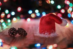 Red Christmas hat and pine cones on the table. On a background garlands Stock Photography