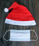 Red Christmas hat,white medical mask,background,new year,happy new year 2021,old year,pandemic