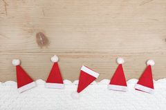 Red christmas hats, crocheted snow on wooden background Stock Photos