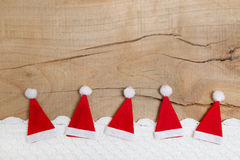 Red christmas hats on wooden background for a greeting card Stock Photos
