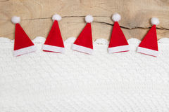 Red christmas hats on wooden background for a greeting card Royalty Free Stock Photo