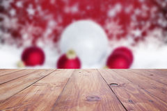 red christmas holiday background with empty wooden deck table over winter bokeh