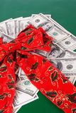 Red Christmas Holiday Bow on top of US Paper Currency Royalty Free Stock Images