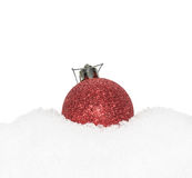 Red Christmas New Year bauble, ball lying on the white snow Stock Image