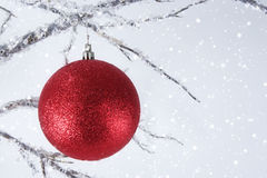 Red Christmas Ornament. A glittery red Christmas ornament hanging on crystal covered branch with falling snow, stars and snowflakes on light blue background royalty free stock image