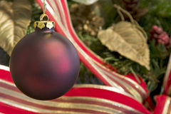 Red Christmas Ornament. Hanging in front of a beautiful wreath with shallow depth of field Royalty Free Stock Photo
