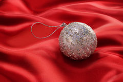 Red Christmas Ornament Background. A silver Christmas bauble ornament on a red satin background stock images