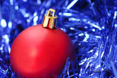 Red Christmas ornament on blue garland Stock Photos