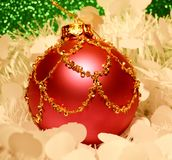Red christmas ornament with gold. Over white and green stock photo