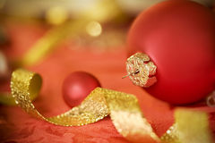 Red Christmas ornament and gold ribbon Royalty Free Stock Photography
