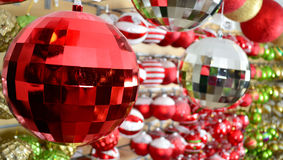 Red christmas ornament hanging from a tree. A red christmas ornament hanging from a tree with golden lighting with bokeh in the background Royalty Free Stock Images