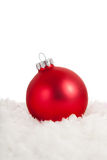A red Christmas ornament in snow Stock Photo