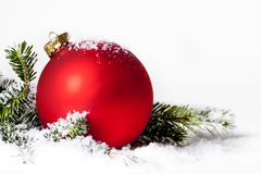 Red Christmas Ornament Snow Pine. A red Christmas ornament nestled in pine bough with snow royalty free stock photography